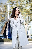 Young woman with shopping bags standing