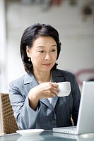 Businesswoman drinking coffee while looking at laptop