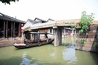 Asia, China, Zhejiang Province, A boat makes its way through Wuzhen water town