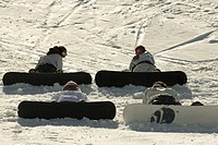 Four young snowboarders sitting on ski slope, rear view, one looking over shoulder