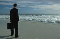 Businessman in full suit standing on beach, looking at sea