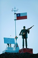 Soldier figurine standing beneath Chilean flag, holding rifle