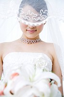 Young bride with veil covering her face