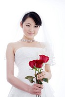 Young bride holding three roses against white background, front view