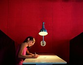 Woman sitting in booth, writing