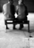 Man and woman sitting on bench, talking, rear view, defocused