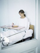 Mirror with reflection of woman sitting up in hospital bed, eating meal from tray