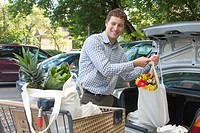 Young man loading groceries in cloth bags, into car, Winnipeg, Canada