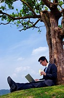 Young businessman leaning against tree using laptop