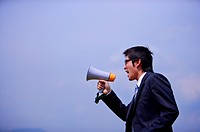 Young businessman holding megaphone against blue sky