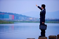 Young businessman holding briefcase pointing at distance