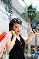 Young woman photographing herself at shopping mall