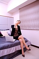Young woman stretching neck while working at home