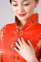 Young woman in cheongsam, hand on chest