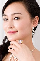 Smiling young woman wearing jewelry, hand on chin, close_up