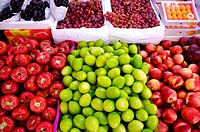 Fresh fruit, including green dates, wax apples, peaches, loquats, and grapes, on display in boxes in a market stall