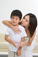Young mother and little boy making heart shape with fingers