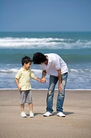 Young father holding little boy´s hand and standing on the beach