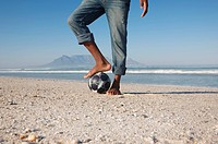 Mans foot on soccer ball beach scene