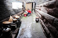 Chinese woman preparing food in a outdoor kitchen setup in the narrow alley between two houses, Lizhuang Ancient Town, Sichuan Province, China