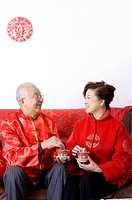 Elderly couple in traditional clothes holding tea cup and smiling at each other