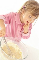Little girl preparing a pancake batter