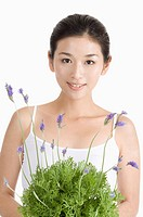 Young woman holding lavender and looking at the camera, portrait