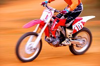 Young man motocross over field.