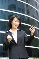 Businesswoman looking at mobile phone and smiling happily