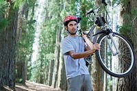 Man carrying bicycle in forest