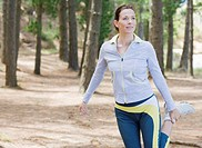 Woman stretching before run in forest