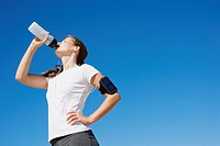 Woman runner drinking from water bottle