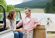 Couple sitting in jeep near lake