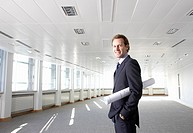 Businessman standing in empty office holding blueprints