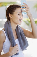 Tired woman cooling off with water bottle