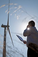 Businessman standing beneath wind turbine