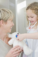 Girl pretending to listen to stuffed animals heartbeat with toy stethoscope