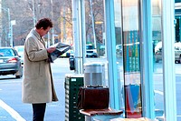A business man reading news paper in the city.Agent 109 Ewing