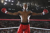 African boxer celebrating his victory by his arms outstretched