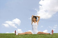 Young Woman Stretching Shoulders while Sitting on Grass