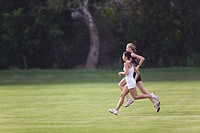Two Women Running Together on Grass