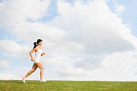 Young Woman in tank top jogging on grass (thumbnail)