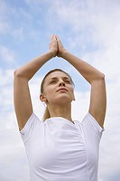 Young Woman meditating in a tree pose