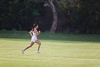 Young Woman in tank top jogging on grass