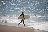 Young man running toward sea with his surfboard