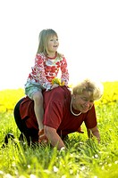 Kleines Maedchen reitet auf der Grossmutter, little girl riding her grandmother