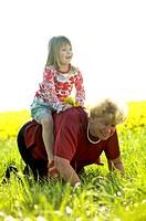 Kleines Maedchen reitet auf der Grossmutter, little girl riding her grandmother