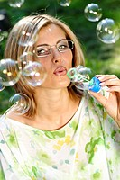 Junge Frau blaest Seifenblasen, young woman blowing bubbles