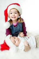 Zwei Kinder mit Nikolausmuetzen, two children wearing Santa Claus hats