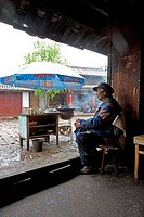 Naxi woman sitting in a chair, Suhe, Lijiang, Shangri_La County, Yunnan Province, Tibet, China